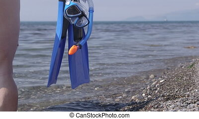Woman with snorkeling set going to swim in sea - Woman with...
