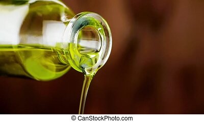 close-up of pouring olive oil with the bottle on wood...