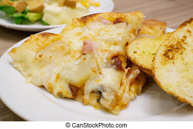 Closeup view of an appetising ham and pineapple Italian pizza with garlic bread and salad