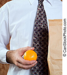 Healthy Orange Snack - Closeup of a businessman holding his...