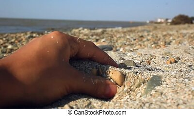 womans hand touch and pour sand in the beach at sunlight -...