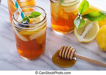 Homemade honey iced tea in mason jars with straws