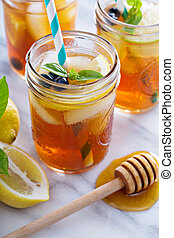 Homemade honey iced tea in mason jars with straws
