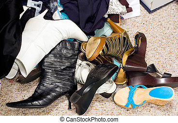 Different types of shoes on a cluttered closet floor