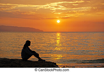 Young girl sitting on the rocks an watching the sun goes...