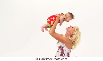 Happy Mother Holding Her Baby Son Aloft - Portrait of a...