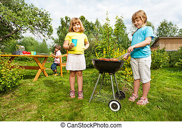 Two girls near grill making BBQ in the garden