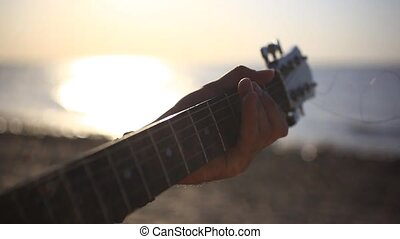 Musician hand playing guitar in the beach during sunset on...