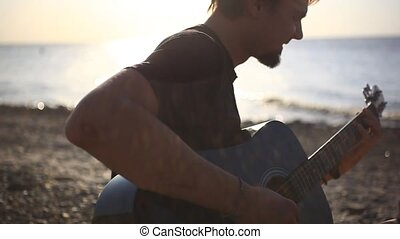 Bearded musician playing guitar in the beach during sunset