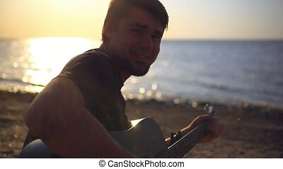 Bearded musician smiles speaks plays guitar in the beach...
