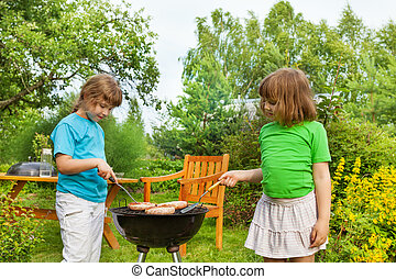 Two girls near BBQ grilling meat in the garden