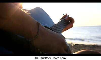 Musician hand playing guitar and he's sings song in the beach during sunset on blurred background and sunlight in sea. Video have a sound