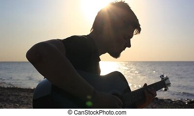 Silhouette of Bearded musician playing guitar in the beach...