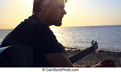 Brutal bearded musician smoking a cigarette on the beach at sunset. He's going to play the guitar