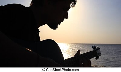 Silhouette of Bearded musician playing guitar in the beach during sunset