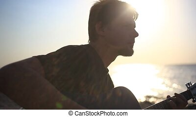 Bearded musician playing guitar in the beach during sunset...