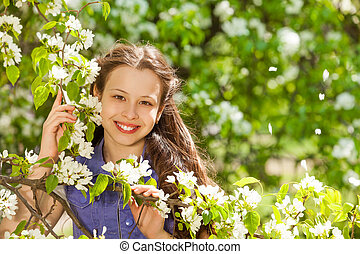 Smiling teenager girl holding white pear flowers - Smiling...