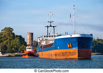 Cargo ship with tug boat - Cargo ship out of the harbor.