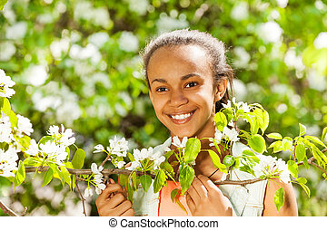 African teenager girl holds white pear flowers - Beautiful...
