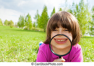 Funny boy smiles through magnifier, lays on grass - Funny...