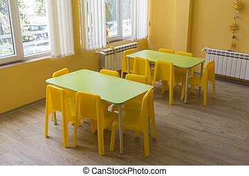 Kindergarten classroom with small chairs and tables for the...