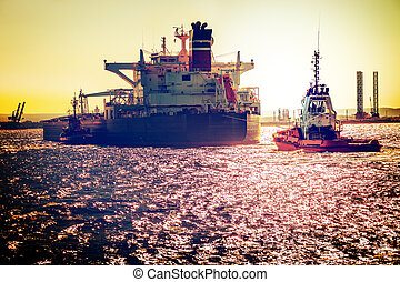 Ship on sea at sunset - Tanker ship with tugboats on sea...