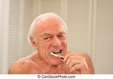 Elderly man brushing his teeth  in front of a mirror