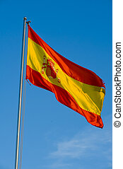 spanish flag on a pole against blue sky