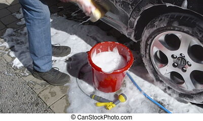 Car Care - Man washing a car by hand using a sponge