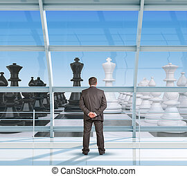 Businessman looking at chess through window, interior view