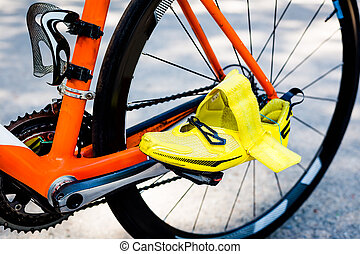 Wheel of the bicycle,orange frame,yellow cycling shoes