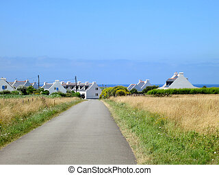 Road to village at the coast of ocean. Brittany, France