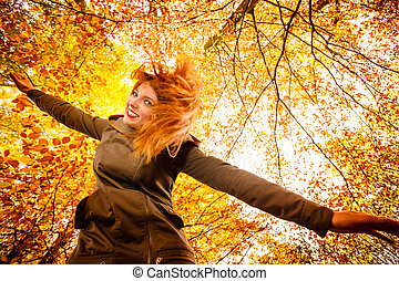 Unusual angle of young woman in autumn park - Season and...