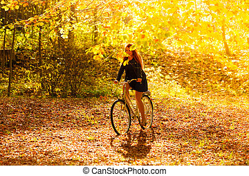 Beauty girl relaxing in autumn park with bicycle, outdoor -...