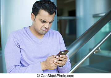 Grumpy man text messages and emails - Closeup portrait,...