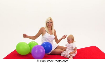 Mother And Baby Playing With Bunch of Multi-Colored Balloons