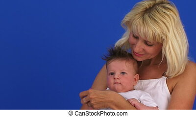 Happy Fair Haired Woman Holding Her Small Baby Boy On Hands...