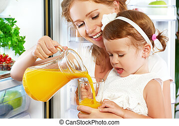 happy family mother and baby daughter drinking orange juice...