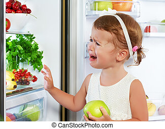 little girl child is crying and acting about fridge with...