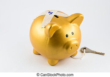 Piggy bank in gold color is locked on its back The key hold...