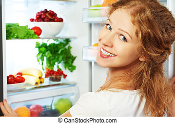 Happy woman and open refrigerator with fruits, vegetables...