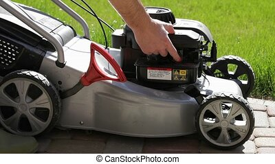 Running Gasoline Mowers. - Man's hand pushing the red button...