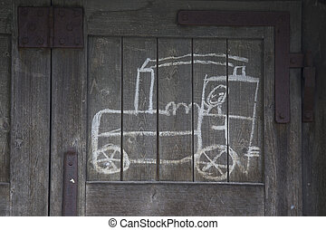 childs drawing of a train on an old wooden wall