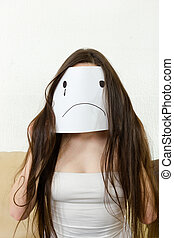 Adult girl cover her face with smile drawn on paper with one...
