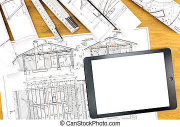architect workplace with tablet blueprint and rolls of plans