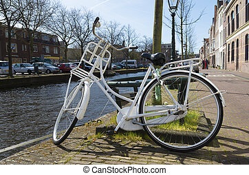 white bicycle along a canal in Leiden, netherlands