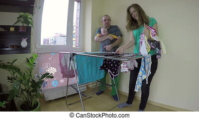 family baby clothes dryer - young family mother and father...