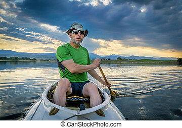 canoe paddler on lake at susnset