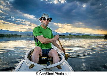 canoe paddler on lake at susnset