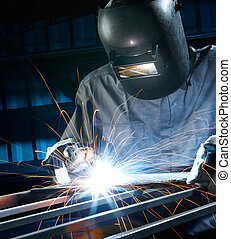welding in workshop - man welding with reflection of sparks...